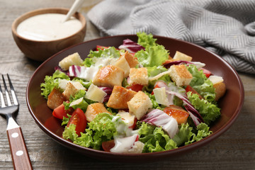 Delicious fresh Caesar salad on wooden table