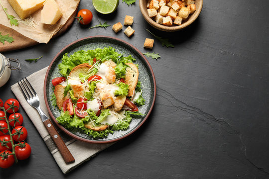 Delicious fresh Caesar salad on black table, flat lay. Space for text