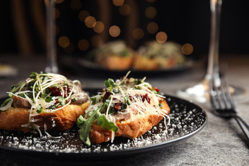 Delicious bruschettas with beef and cheese on grey table, closeup