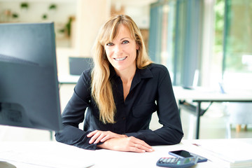 Portrai tof middle aged businesswoman sitting at office desk while looking at camera and smiling