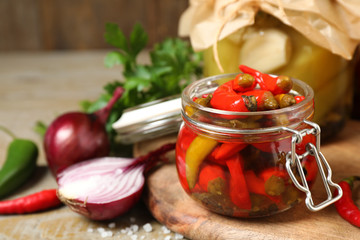 Canvas Prints Hot chili peppers Glass jar with pickled peppers on wooden table