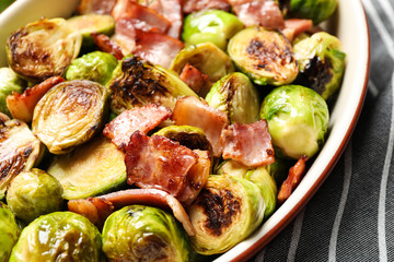 Delicious Brussels sprouts with bacon in baking pan, closeup