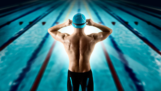 Swimmer jumping from starting block in a swimming pool