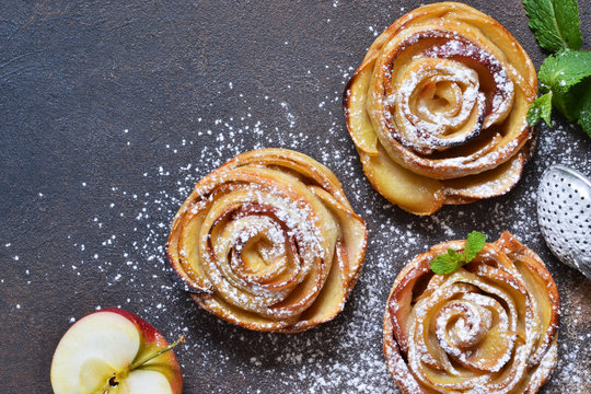 Dish of apple roses baked in puff pastry on a dark concrete background with apples. View from above