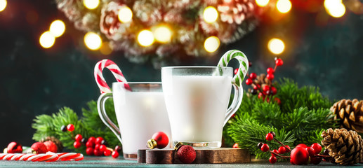 Hot winter white drink with candy sticks, Christmas or New Year decorations, dark background, rustic style, copy space