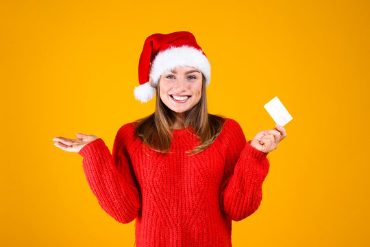 Close up portrait of young beautiful woman with light make up on, wearing red knitted sweater & santa claus hat. Attractive female in winter knitwear outfit, isolated on yellow background. Copy space