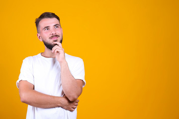 Young handsome man with facial hair posing yellow gray wall with a lot of copy space for text. Portrait of confident bearded male, wearing blank white oversized t-shirt. Isolated, background.
