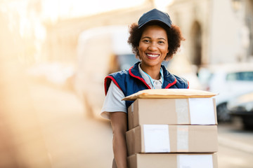Portrait of happy African American deliverer with packages. Wall mural