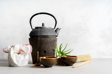 Simple still life with tea set, present, gift, scattered tea, bamboo Mat, sticks, incense. Asian background with space for text.