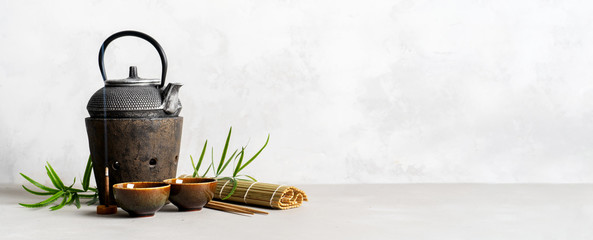 Foto op Plexiglas Thee Simple still life with tea set, scattered tea, bamboo Mat, sticks, incense. Asian background with space for text.