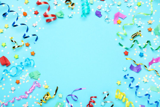 Colorful ribbons with paper stars and confetti on blue background