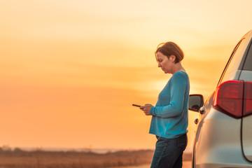 Woman text messaging roadside assistance help after car broke down