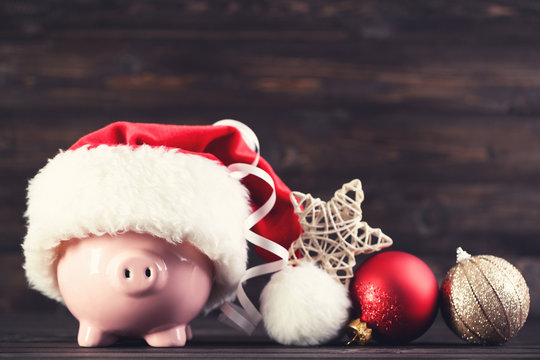 Red santa hat with piggybank and ornaments on brown wooden background