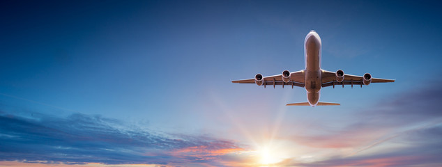 Aluminium Prints Airplane Commercial airplane flying above dramatic clouds during sunset.