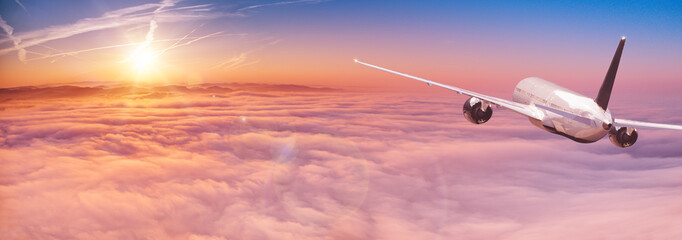 Poster Avion à Moteur Commercial airplane flying above dramatic clouds during sunset.