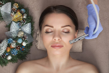 Poster de jardin Spa Beautician makes a procedure Microdermabrasion to beautiful woman. Next to her are Christmas decorations. New Year's and Cosmetology concept.