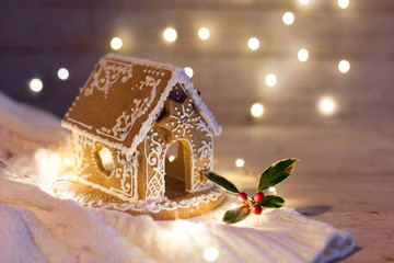 Christmas gingerbread house at night, cozy decorations on wooden and knitted background with glares. Cozy house in warm light with holly berries and white ornaments.