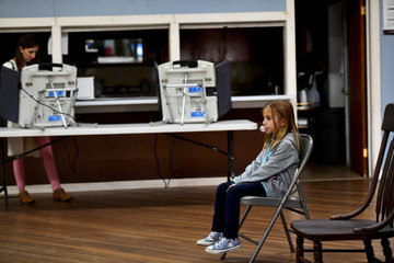 Jenna Heidlebaugh, 7, blows bubble gum while waiting for her (L) mother, Jennifer, to cast her ballot in state and local elections at the Barry Township Building in Barry Township
