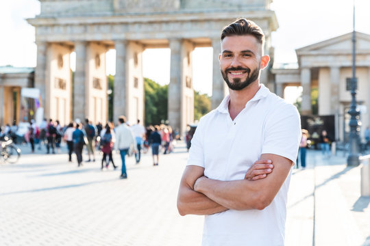 Portrait of smiling young man standing in front of Brandenburger Tor, Berlin, Germany