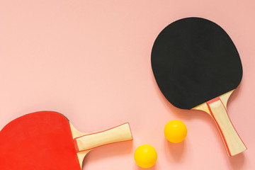 Black and red tennis ping pong rackets and orange balls isolated on a pink background, sport equipment for table tennis