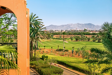 View of Marrakech from a golf resort with green fields and palms in Morocco