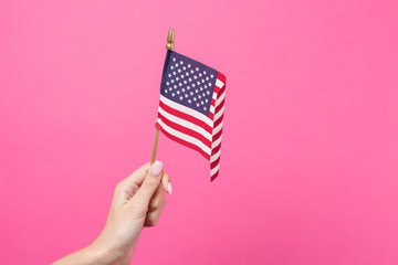 Hand holding american flag on pink