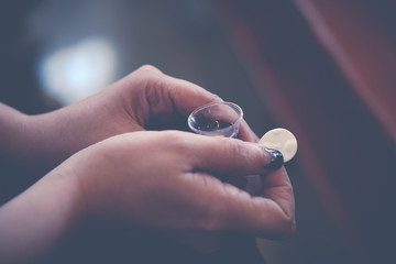 Woman holding wine in a Holy communion.