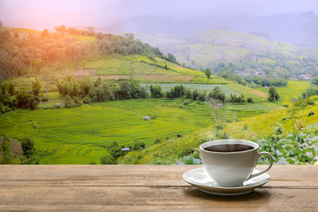 Black coffee in white cup on wooden table with  beautiful nature in morning  beautiful landscape background
