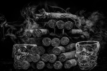 Large stack of hand rolled cuban cigars against dark backround with smoke and human skul shaped shot glasses.