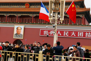 Visitors take pictures under Chinese and French flags fluttering near the Tiananmen Gate as France's President Emmanuel Macron visits China, in Beijing
