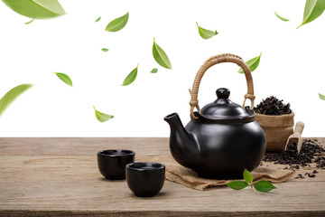 Photo sur Toile The Cup of hot tea with teapot, flying green tea leaves in the air and dried herbs on the wooden table isolate white background, Organic product from the nature for healthy with traditional