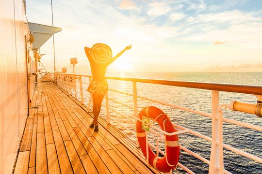 Luxury cruise ship travel elegant woman having fun carefree on deck enjoying watching sunset on Europe cruising destination vacation. Summer european mediterranean cruiseship sailing away on holiday.