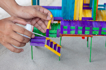 Hand of men is applying glue to connect colorful popsicle sticks into the toy house.