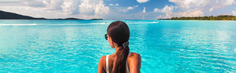 Luxury beach ocean vacation elegant lady walking over pristine turquoise ocean crystalline water in paradise honeymoon travel destination panoramic banner. Cruise background tourist woman.