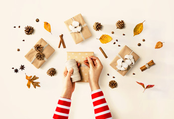 Person making present boxes with autumn theme