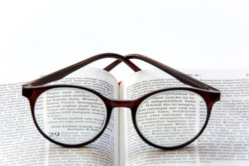 Open holy bible in bahasa Indonesia (Yeremia 29:11) on white background with glasses close up