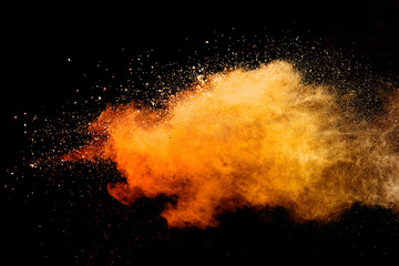 Abstract orange powder explosion isolated on black background.