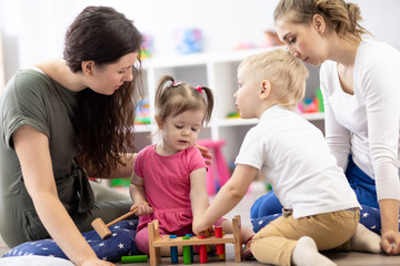 Toddlers and their mothers playing with colorful educational toys in nursery room