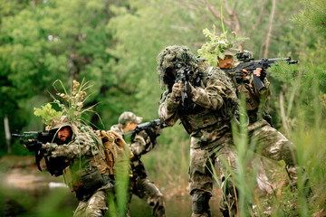 Soldiers in a combat situation. Men play airsoft.