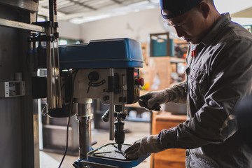 Asian technician skilled,he uses a metal lathe.