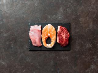 Raw turkey breast fillet, salmon steak and beef ribeye steak on black slate board over dark background. Top view or flat lay. Protein food, keto, carnivore, paleo diet concept. Copy space. - fototapety na wymiar