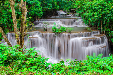 Spoed Fotobehang Bos rivier Travel to the beautiful waterfall in tropical rain forest, soft water of the stream in the natural park at Kanchanaburi, Thailand.