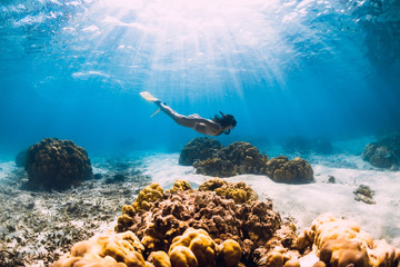Woman freediver glides over sandy sea with yellow fins in transparent sea. Freediving in Mauritius Wall mural