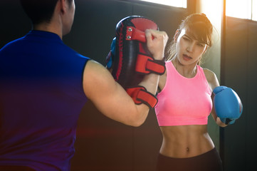 Asian sport woman in action of being practice boxing with personal trainer or partner exercise in gym studio, couple lover practice boxing together