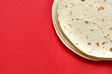 Tortillas on red background. A pile of  baked blank corn tortilla wraps on a color background with copy space. Top view or flat lay for use as a cooking, mexican restaurant or travel background.