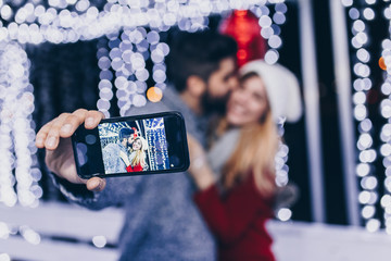 Beautiful young romantic couple taking selfie photo during ice skating.