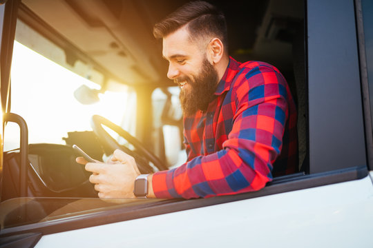 Young handsome bearded man using smart phone in his truck.