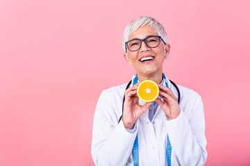 Dietician holding an orange. Smiling nutritionist holding a sliced orange, vitamins and healthy diet concept. Good medical healthcare nutrition concept.