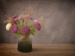 Vase with beautiful chrysanthemum flowers on wooden table. Holiday card.
