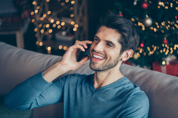 Close up photo of joyful guy speaking cellphone tell congratulations with newyear enjoy christmas atmosphere sit couch in house with bright magic miracle lights